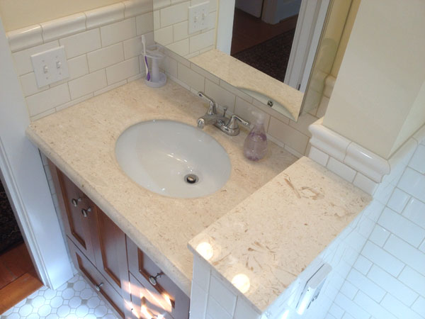 White tile classic bath design with natural stone vanity countertop and chrome fixtures