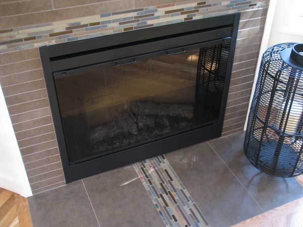 Fireplace tile with a modern approach using stone, porcelain, and glass.